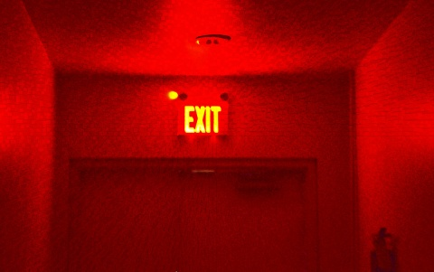 a red exit sign lights up a dark doorway, all red