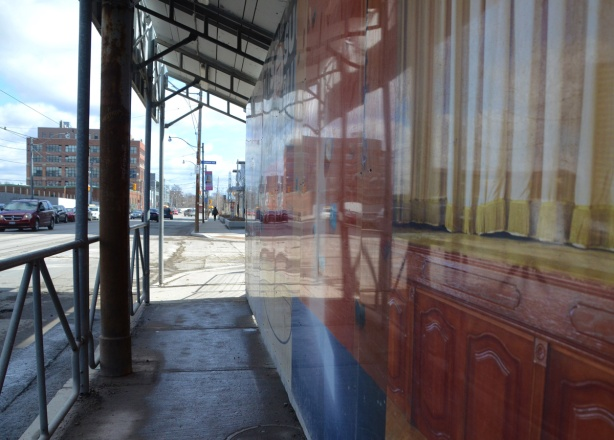 reflections in hoardings that are covered with a picture of yellow curtains and brown wood, sidewalk beside the hoardings and a wood structure over the sidewalk