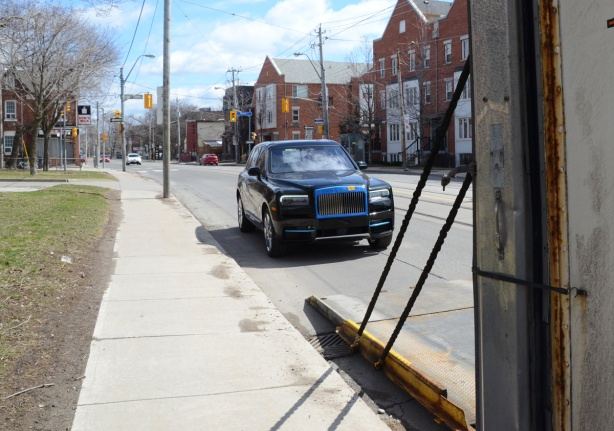 new rolls royce parked on the side of a street after being unloaded from a truck