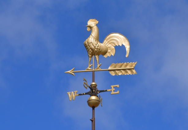a gold coloured weather vane with a rooster on it, bright blue sky in the background