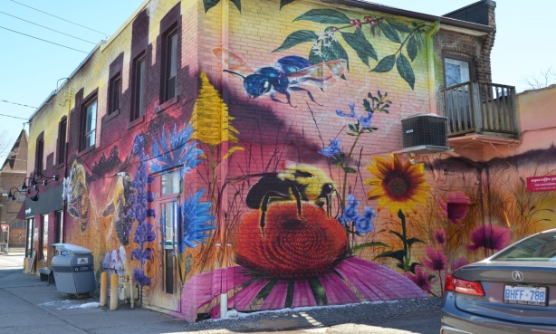 part of a nick sweetman pollinators mural, corner of supercoffee building, several bees and many flowers
