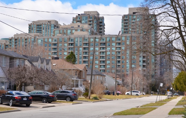 apartment building in the background, a street of single family dweelings in the foreground, early spring so no leaves on the trees, a few cars parked in driveways