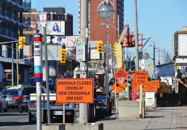 sidewalk, many orange construction signs cluttering the sidewalk, bus stop, traffic on the street,