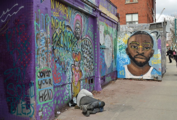 a man sleeping on the sidewalk in front of a wall covered with street art, graffiti and art in memory of Andre Alexander who was an artist who worked in Kensington