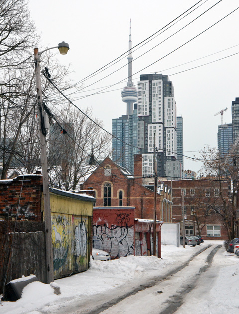 snowy alley with two ruts for wheels of cars, garages with graffiti on left side, small church near the end of the alley, large condo and CN Tower in the distance
