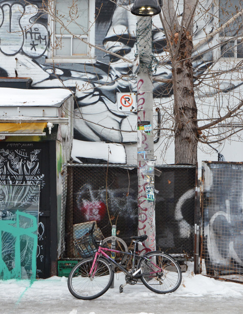 a bike locked to a tree on a sidewalk in front of a mural on a building, snow,