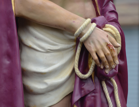 close up of a statue of Jesus just showing his hands and arms tied with rope
