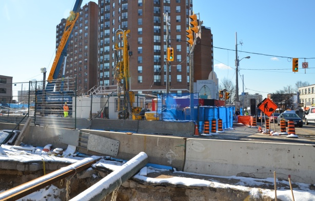 red brick apartment buildings with crosstown LRT construction in front of them.