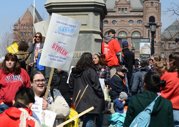 person holding a placard protesting Doug Fords proposed cuts to education funding, Crowds at a protest at Queens Park,