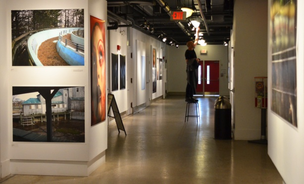 part of the third floor hallway gallery space at Artscape Youngplace with large colour photos tacked to the wall, a man on a ladder adjusts the lighting