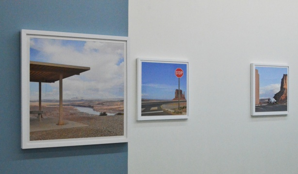 three paintings by Emmanuel Monzon on a wall in gallery, pictures of empty places, or where urban sprawl seems to take over deserted places