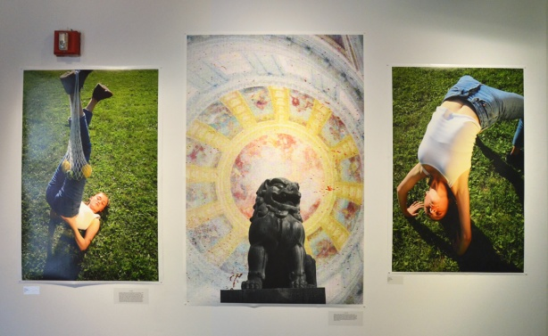 three photographs hanging on a wall. On either side is a picture of a woman in a pose, on green grass outside by Julia Kerrigan. In the middle is a black statue, Asian lion, in front of a light pastel coloured circular pattern