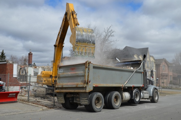 a yellow digger loading rubble from a house demolition into a dump truck