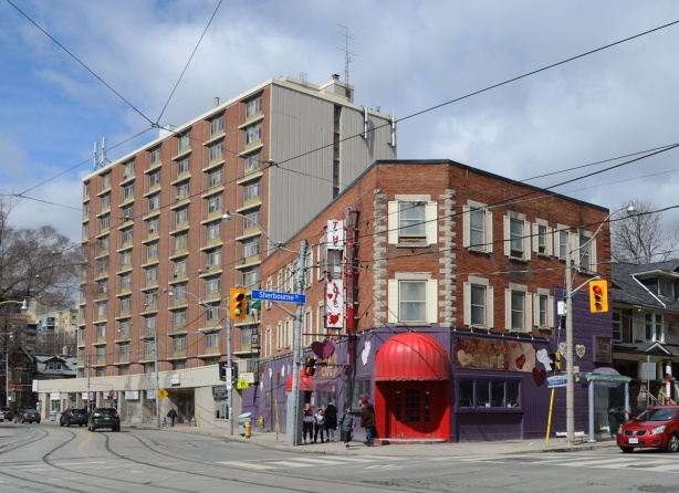 the True Love Cafe on the corner of Dundas and Sherbourne, purple walls on exterior ground floor, large red awning over entrance,