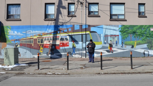 mural of the evolution of TTC streetcars and LRT vehicles, painted by Jim Bravo in 2017, stylized but realistic looking