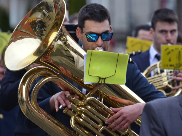 a young man plays a tuba in a marching band he is wearing bright blue sun glasses