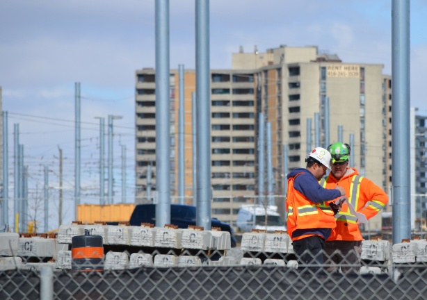 two workmen in hard hats and orange work vest look at paperwork on a construction site.