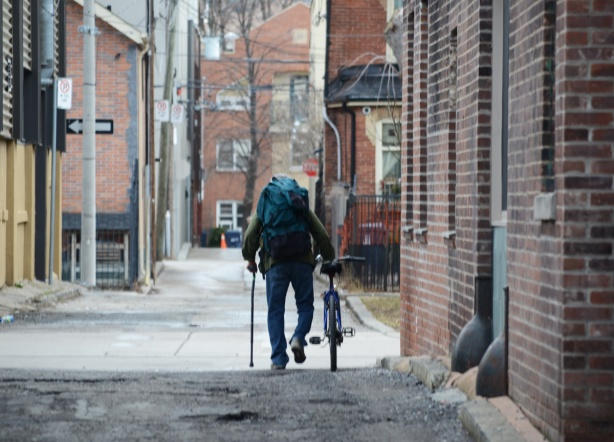 a man with a cane in one hand, and pushing a bike with other walks down an alley. he also has a backpack on his back