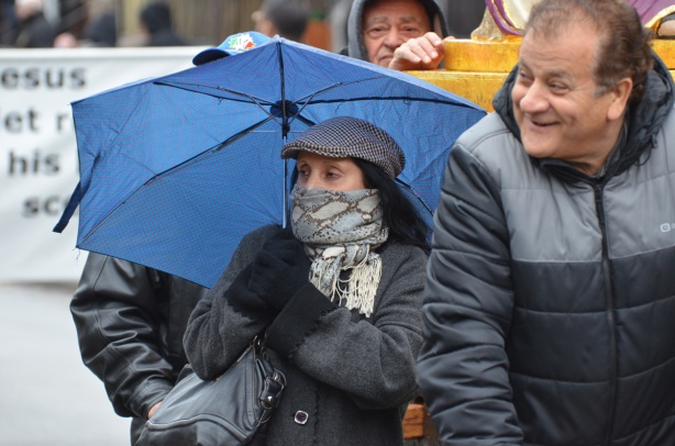 a woman bundled up in grey tam and scarf over the bottom of her face and carrying a blue umbrella, walking with some men in a passion of christ good friday procession