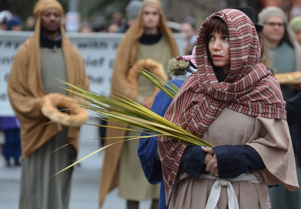 a woman in long bronw robes and plaid loose fitting head scarf, carrying long palm fronds in a parade