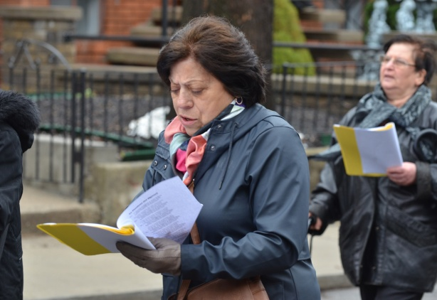 two women singing, reading from pages in a yellow folder as they walk on the street