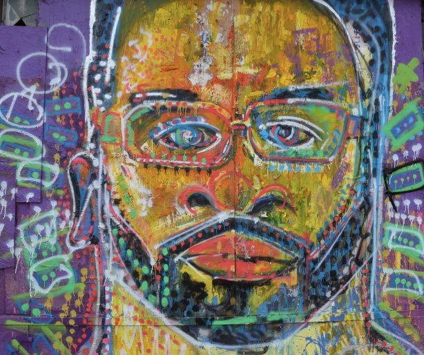 large painting of a face, street art, yellowish skin, small moustache and beard, glasses, eyes looking straight ahead