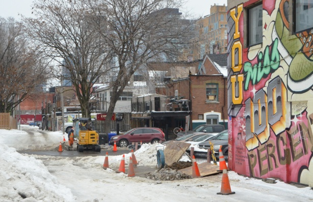 workmen on the side of a street, windter, snow, alley with a mural on the right,