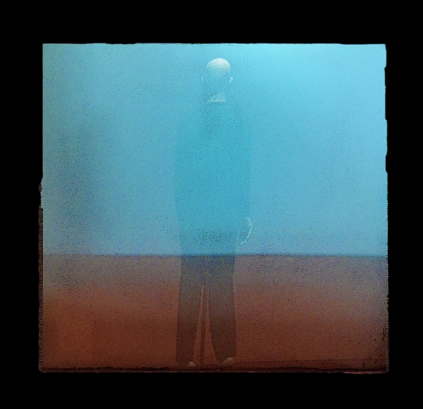 reflections in a window, vague shape of a man, blue background on top and orangey brown on the bottom