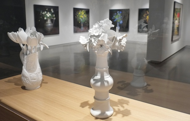 2 white 3 D printed sculptures of flowers in a vase, in a gallery, with large pictures, in colour, of bouquets of flowers in vases on tables