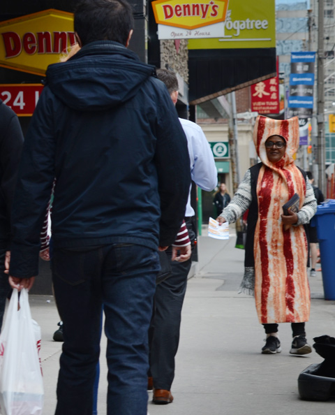 a woman is dressed in a bacon costume and standing on the sidewalk on Dundas Street giving out flyers