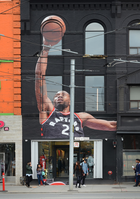 mural of a basketball player, Raptors #2, shooting a basketball with one hand, large mural on the upper two storeys of a store, people on sidewalk below