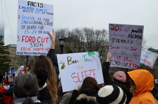 protest signs at a rally including one that says Bees and trees not sleaze
