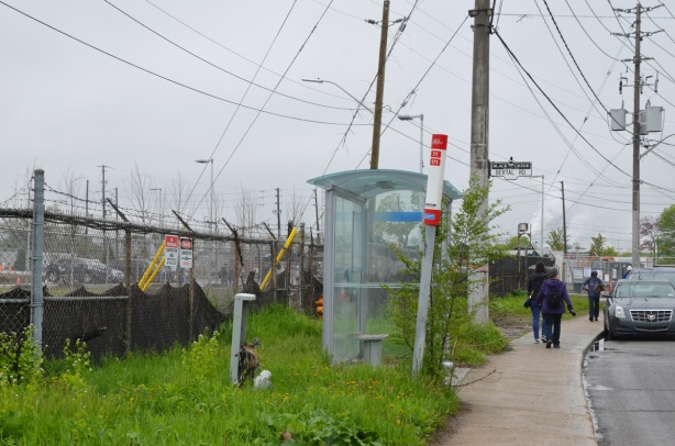 bus shelter at Bertal Rd near the new facility, barbed wire fence around the building, grass and weeds around the shelter