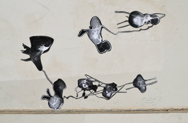 seven black and white photo paste ups that look like ameobas or primitive life forms on a concrete wall, outdoors,