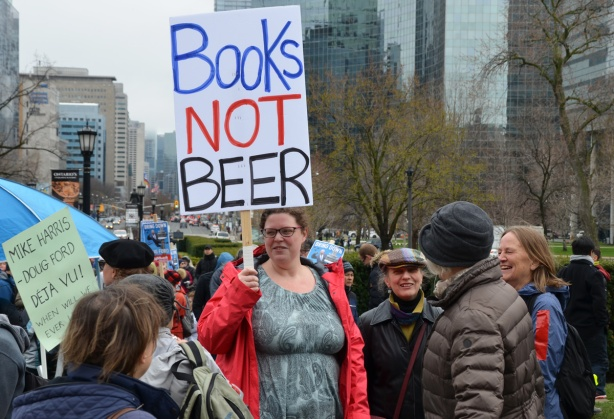 a woman holds a sign that says books not beer
