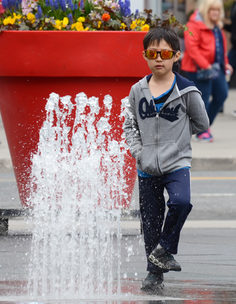 a young boy in sunglasses stands on one foot in front of a water fountain at Dundas square