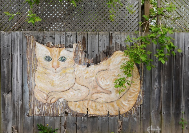 large painting of a yellow and white cat on canvas stapled to a wood fence, outdoors.