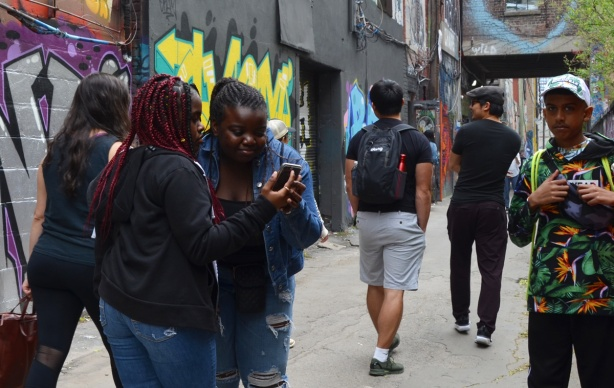 two girls checking a video on a phone, other people nearby, in graffiti alley