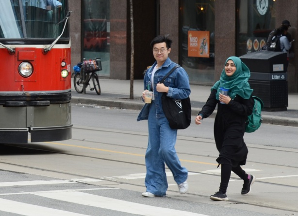 a couple crosses a street by a streetcar, an Asian man and a woman in a teal head scarf