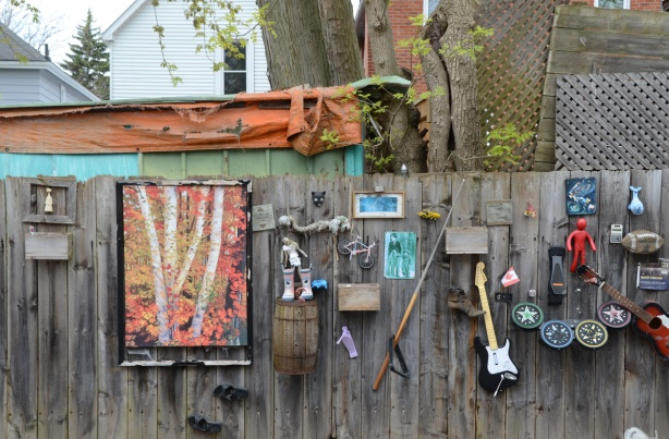 many found objects attached to a wood fence, outside,