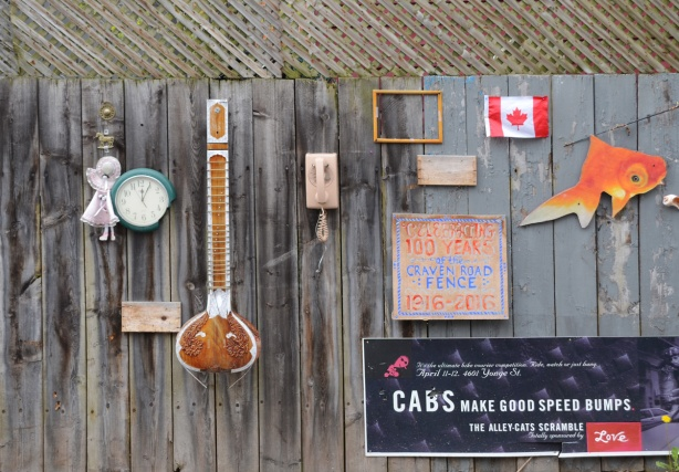 objects attached to a wood wall, outside, small flag, musical instrument, clock, sign,