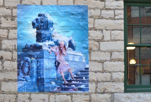picture on a stone wall, blue tones, lion sculpture, sitting beside flight of stairs, woman leaning against lion, cigarette in her mouth, food in the other hand, garbage strewn on the stairs around her feet