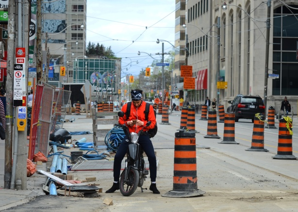 a cyclist with an otange shirt sits on his bike while looking at his phone. He's stopped behind an orange and black striped construction cone on the side of a street