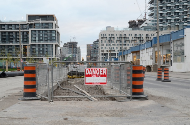 danger sign on construction zone in the middle of the street, Queens Quay, looking west along the street towards downtown toronto