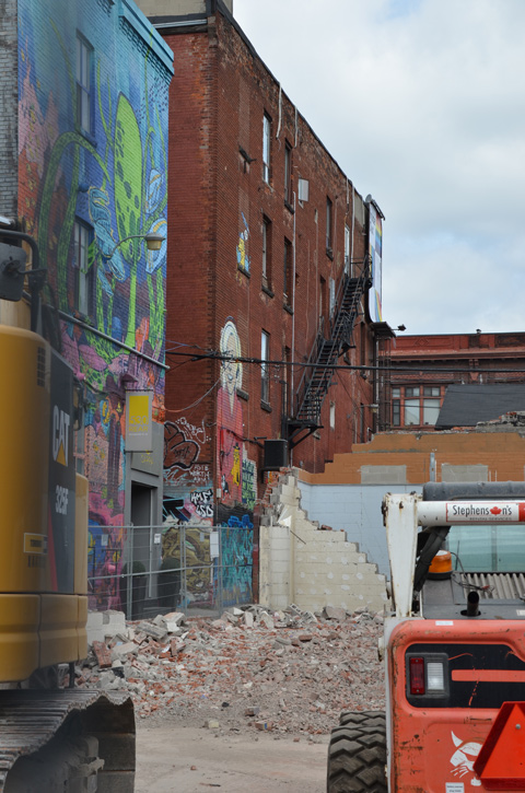 demolition of building in graffiti alley, remaining buildings in the background