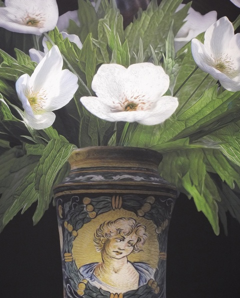 white flowers and greenery in a vase with a picture of a young man on it, part of a larger photograph by T.M. Glass in a gallery