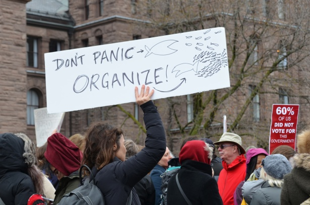 in the middle of a protest crowd, a woman holds up a sign that says Don't panic, organize