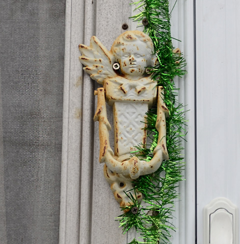 old rusty white door knocker with metallic green garland beside it