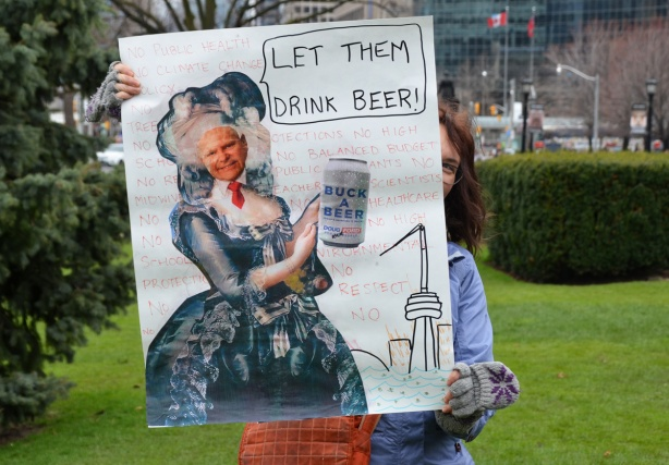 a woman holds up a sign at a protest that says let them drink beer. with a picture of Doug Ford as Marie Antoinette