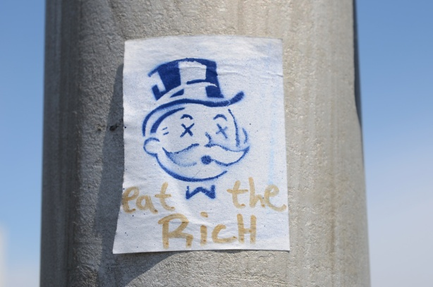 a small paste up on a utililty pole, blue stencil of the monopoly guy's head, top hat and X's for eyes, under his head are the words eat the rich